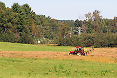 Farm tractor in hay field with sunshine style hay rake, summer hay crop scenic