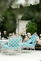 White wrought-iron armchairs with turquoise cushions are grouped beneath a parasol on a terrace in the garden