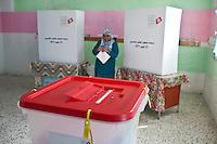 23 ottobre 2011 Tunisi, elezioni libere per l'Assemblea Costituente, le prime della Primavera araba: una donna esce dalla cabina elettorale con la scheda in mano e si dirige verso l'urna.
