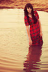 Young woman with long dark hair wearing red dress standing alone in a lake