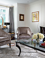 A traditionally furnished sitting room with upholstered seating arranged around a glass topped coffee table.