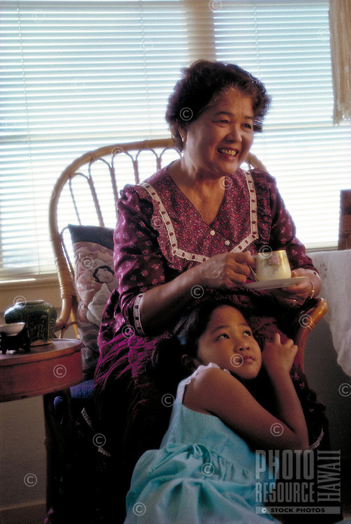 Japanese American grandmother and young granddaughter show affection for one another.