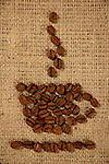 Conceptual artistic pattern of a cup of coffee made from coffee beans on a sacking background