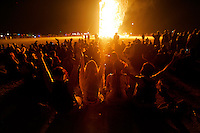 BLACK ROCK CITY, NV - AUGUST 30, 2008: Participants watch as the Man burn during closing ceremony including pyrotechnics and fire dancing. The finale of the Burning Man event, August 30, 2008. The annual arts festival, which encourages participation and creativity, attracts over 30,000 participants to the Nevada desert each year.