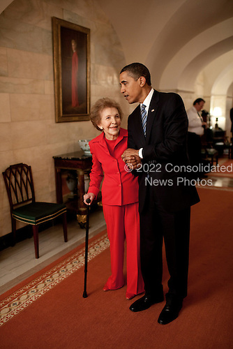 Washington, DC - June 2, 2009 -- United States President Barack Obama and former First Lady Nancy Reagan walk side-by-side through Center Hall in the White House, June 2, 2009. To the left of Mrs. Reagan hangs her official White House portrait as First Lady.  <br /> Mandatory Credit: Pete Souza - White House via CNP