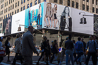 Pedestrians cross 42nd street in New York on Wednesday, September 17, 2014 past a billboard advertising a Zara clothing store that is currently under renovation. Zara announced that it will start using RFID chips in its merchandise to keep better control over its inventory. Zara has 2000 stores worldwide and half of them will be using the technology by the end of 2014. (© Richard B. Levine)