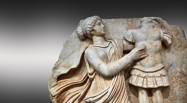 Close up of a Roman Sebasteion relief  sculpture of a Goddess inscribing a trophy, Aphrodisias Museum, Aphrodisias, Turkey. <br /> <br /> A draped goddess strides forward to inscribe a military trophy to which is bound a kneeling female captive. The goddess is probably a personification such as Honour, Virtue or Courage.
