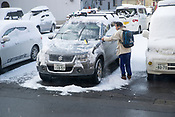 A man clearing snow off of his car at Yudanaka, Nagano.