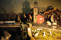 "Switzerland. Canton Tessin. Vira Gambarogno. The old town shows an exhibit of various Nativity scenes, illuminated at night for the Christmas holiday season. A Nativity Scene, may be used to describe any depiction of the Nativity of Jesus in art, but in the sense covered here, also called a crib or in North America and France a crèche (meaning ""crib"" or ""manger"" in French). It means a three-dimensional folk art depiction of the birth or birthplace of Jesus, either sculpted or using two-dimensional (cut-out) figures arranged in a three-dimensional setting. Christian nativity scenes, in two dimensions (drawings, paintings, icons, etc.) or three (sculpture or other three-dimensional crafts), usually show Jesus in a manger, Joseph and Mary in a barn (or cave) intended to accommodate farm animals. The scene includes the Magi or Three Wise Men (with or without a camel), shepherds and sheep, and the angels. Train and church.  © 2007 Didier Ruef"