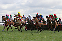 The field in jumping action in the TurfTV Novices Hurdle - Horse Racing at Kempton Park Racecourse