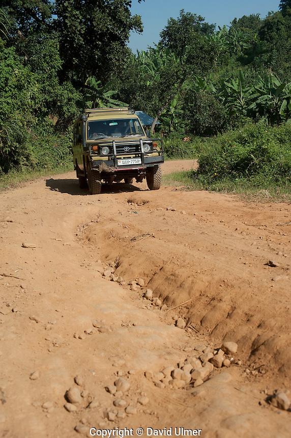 SUV on a rutted dirt road in Bwindi Impenetrable Forest, Uganda.