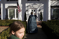 NWA Democrat-Gazette/CHARLIE KAIJO Julia Stilwell, 10, Judy Costello and Malachi Cross, 8, (from left) approach a doorstep to greet neighbors with carols during the Washco Historical Society annual Holiday Open House, Sunday, December 2, 2018 at the Headquarters House in Fayetteville.<br />