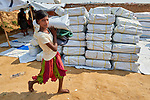 A Rohingya girl carries a tarp, blankets and other items that she received from Christian Aid in the Jamtoli Refugee Camp near Cox's Bazar, Bangladesh. Christian Aid is a member of the ACT Alliance.<br /> <br /> More than 600,000 Rohingya have fled government-sanctioned violence in Myanmar for safety in Bangladesh.