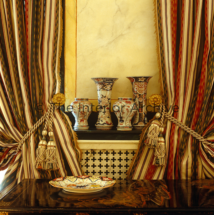 A collection of Chinese porcelain vases are displayed on a radiator between a pair of grand curtains