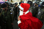 A Palestinian protester dressed in a Father Christmas costume argues with members of the Israeli security forces during a demonstration against the Israeli settlements and demanding for free movement for the Palestinians during the Christmas period near a checkpoint in the West Bank biblical city of Bethlehem on December 23, 2014. Photo by Muhesen Amren