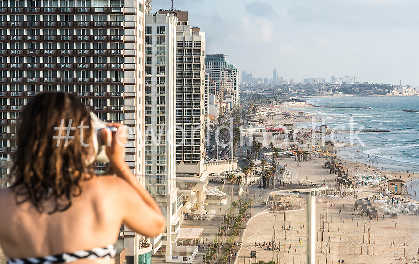 ISRAEL, Tel Aviv, a woman is looking toward Tel Aviv's Promenade and Beaches, Jaffa in the far background