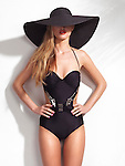 Beautiful young woman wearing a black one-piece monokini swimsuit and a wide brim sun hat covering her face isolated on white wall background