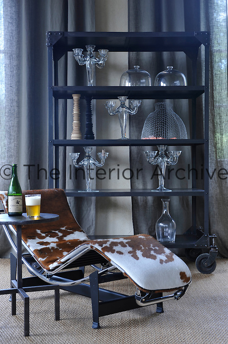 In the living room an industrial-style shelf on large castors displays a collection of delicate glass candelabra behind a cow-hide-covered Le Corbusier chaise-longue
