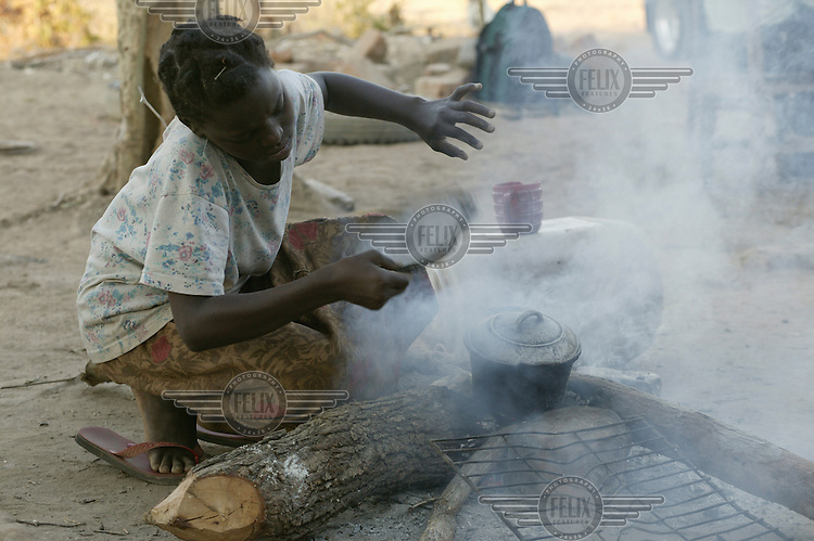 Bridget starts a fire to cook the evening meal of small fish. Many of the farming families here were forcibly moved from their old land which was flooded to create the Kariba dam Hydro Electric station. All the water from the dam is pumped 30km from the lake to the mining town of Maamba, leaving nothing for the nearby villages.