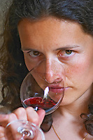 Sylvie Courcelle, daughter to Francis Courcelle, owner and winemaker, tasting a glass of her red wine, looking into the camera Chateau Thieuley La Sauve Majeure Entre-deux-Mers Bordeaux Gironde Aquitaine France
