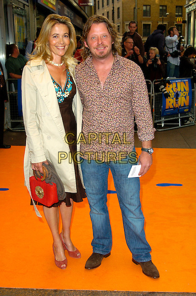 "CHARLIE BOORMAN & GUEST.""Run Fat Boy Run"" premiere at the Odeon West End, London, England..September 3rd, 2007.full length jeans denim brown pattern shirt beige mac trench coat orange bag purse .CAP/CAN.©Can Nguyen/Capital Pictures"