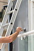 A painter and decorator paints an exterior wall of a house.