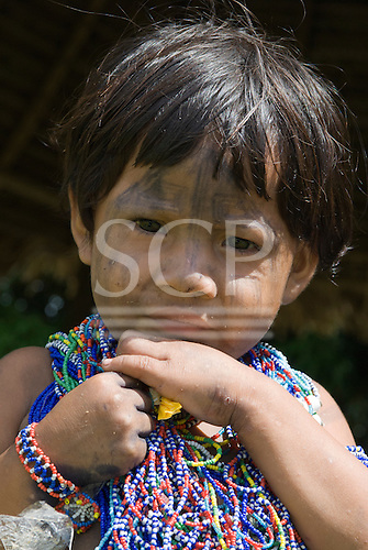 Pará State, Brazil. Aldeia Koatinemo (Assurini). Child with colourful bead adornments.