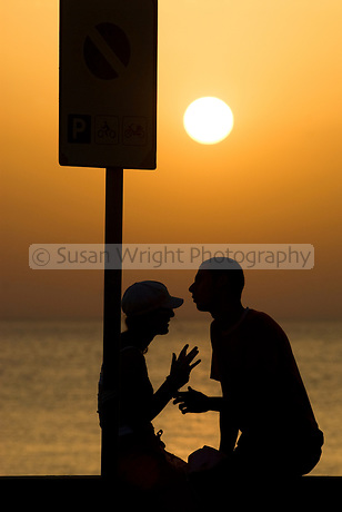 Teenage couple chatting and touching, silhouetted against sunset over sea, Cefalu, Italy