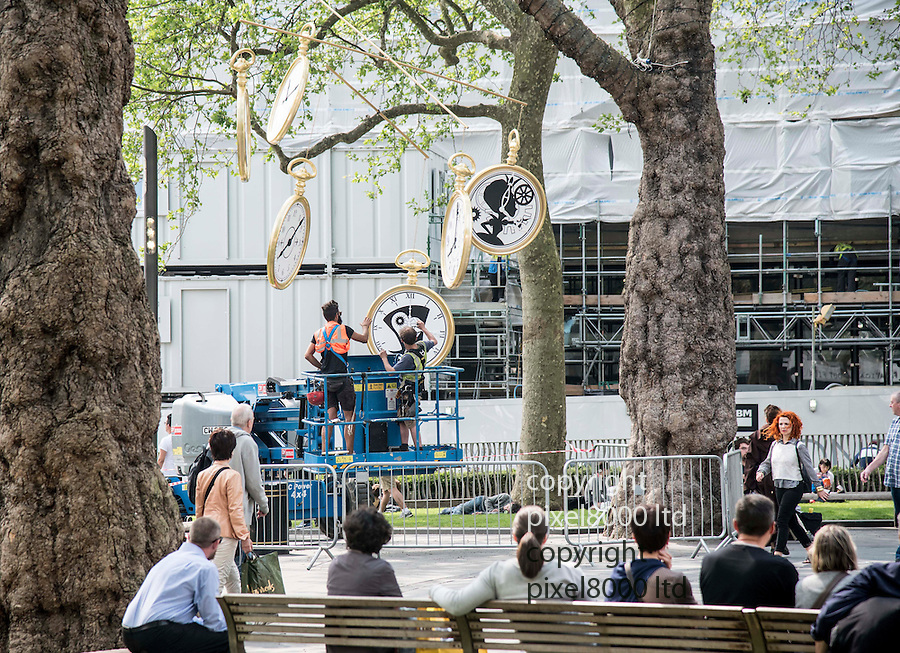 Pic shows:<br /> High winds caused chaos in Leicester Square today as workmen tried to erect a giant mobile made of pocket watches for the premiere of Alice Through the Looking Glass.<br /> Up on a cherry picker the workers had to duck and weave as the giant clocks swung around precariously after being strung for a tree.<br /> Lunchtime picnickers looked on in amusement as the hapless team tried again and again to erect the promotional installation.<br /> At times the huge time pieces whizzed around in the wind and refused to behave.<br /> <br /> <br /> <br /> Pic by Gavin Rodgers/Pixel 8000 Ltd