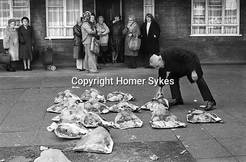 Funeral wreathes, local women gather to watch funeral procession. Wreathes being removed by undertaker.  Hoxton London Uk 1978.