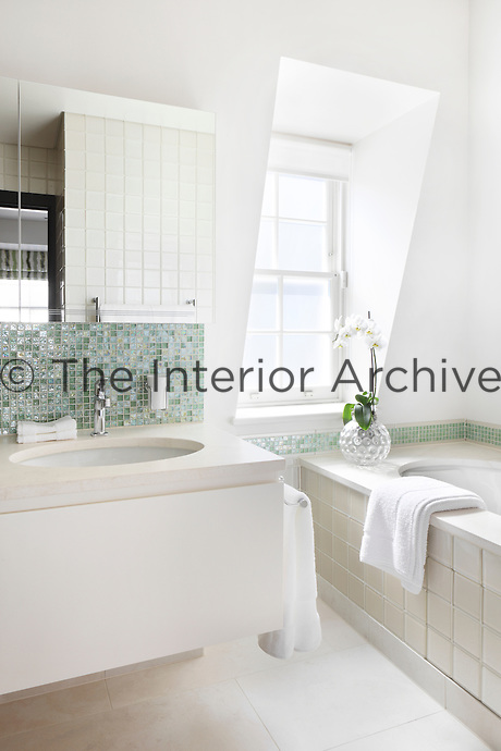 The cream tone of the stone flooring, basin surround and wall tiles bring a warmer tone to the white bathroom