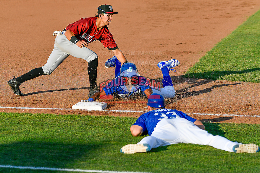 Errol Robinson (9) of the Ogden Raptors hustles towards third base and beats the tag from Manny Olloque (11) of the Idaho Falls Chukars in Pioneer League action at Lindquist Field on June 28, 2016 in Ogden, Utah. The Raptors defeated the Chukars 12-11.  (Stephen Smith/Four Seam Images)