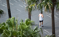 14 SEP 2009 - SYDNEY, AUS - A jogger plots a route between palm trees on Circular Quay (PHOTO (C) NIGEL FARROW)
