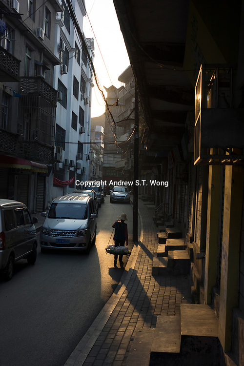 Huanggang, Hebei province, China - An elderly woman carries goods through the old district of Huanggang,  October 2014. Famous Song dynasty poet and politician Su Dongpo used to live there in exile.