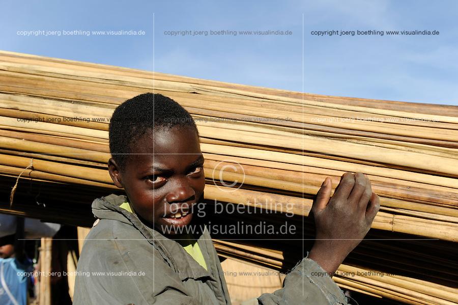 ZAMBIA Barotseland Mongu, Mulamba harbour at river Zambezi floodplain, boy carry sticks / SAMBIA Barotseland , Stadt Mongu , Hafen Mulamba in der Flutebene des Zambezi Fluss, Junge traegt Rohr