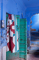 Traditional studded double doors open on to a blue-painted corridor in this Indian haveli