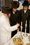 Israel, Bnei Brak. Purim feast at the Premishlan congregation, the Rabbi is lighting the candles. His White robe used rarely, on holidays like Yom Kippur, Purim and weddings of his children, 2005<br />