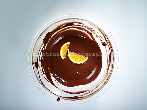 Overhead view of a Pyrex mixing bowl with chocolate sauce and two orange slices