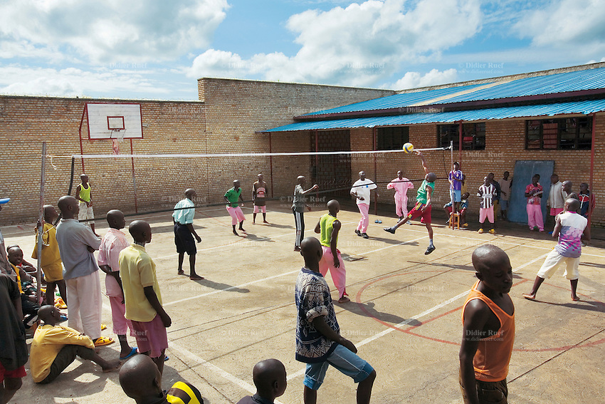 Rwanda. Southern province. District of Muhanga. Central jail of Gitarama. Young boys play volleyball on the concrete playground. Prisoners wear pink clothes.Bricks wall. Minors block. Minors in detention. Detention pending trial and after trial, when sentenced to prison. The non-governmental organization (NGO) Fondation DiDé - Dignité en détention runs the Encademi (Encadrement des mineurs) program. Prison centrale de Gitarama. Quartier des mineurs.  © 2007 Didier Ruef