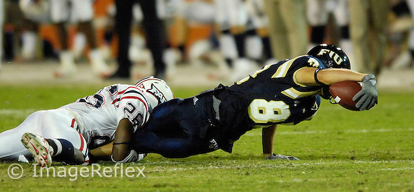 24 November 2007: Florida International wide receiver Greg Ellingson (82) attempts to stretch out for a first down while being tackled by Florida Atlantic cornerback Corey Small (26) during the second quarter of the Florida Atlantic 55-23 victory over FIU at the Orange Bowl in Miami, Florida.