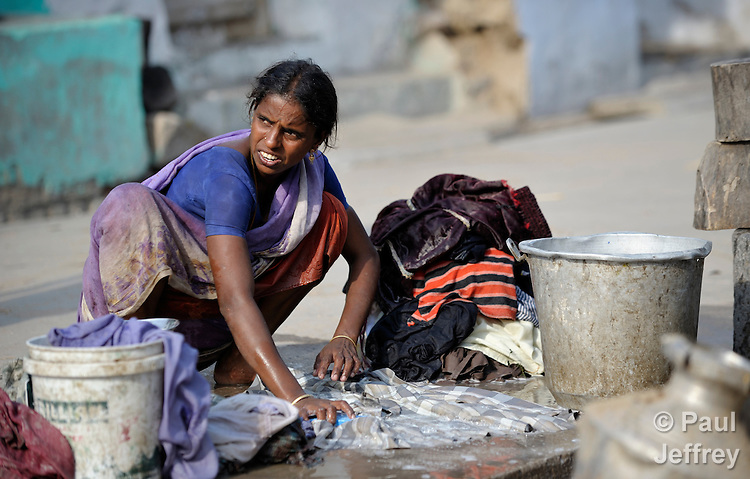 A woman washes laundry on a street in Sathangudi, a village in the southern Indian state of Tamil Nadu.