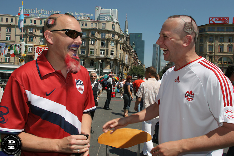 USA National Soccer Team fan Zack Phillips, also known as Mr. Soccerhead, of San Francisco, Calif. shares a laugh with Canadian soccer fan Yuri Smieska of Hamilton, Ontario after Phillips had cut the hair of Smieska into the design of a soccer ball outside the Frankfurt Main Train Station in Frankfurt-am-Main, Germany on Tuesday, June 13, 2006.  The hair cut attracted the attention of many curious travelers. For the previous ten years, Zack Phillips has cut the hair on his head in the design of a soccerball and has even tattoed the design to make it easier to cut. At the 2002 World Cup in Korea Zack cut the hair of Yuri Smieska and Yuri asked Zack if he could do it again this World Cup. They met up outside the train station before Yuri went  to the Korea-Togo FIFA World Cup first round match in Frankfurt-am-Main with some fellow Canadian friends.