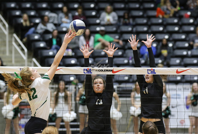 Prosper Eagles senior Haley Killinger (12) attacks as Rouse Raiders seniors Maddie Sheehan (13) and Mackenzie Huntley (11) during the Class 5A high school volleyball state final between Rouse High School and Prosper High School at Curtis Culwell Center in Garland, Texas, on November 18, 2017. Prosper won the match in five sets, (25-18, 21-25, 18-25, 25, 23, 16-14) to win the 5A state championship.