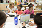 November 15, 2011. Mooresville, NC.. Elena DaCosta, left, a math teacher at East Mooresville Intermediate School, helps a 4th grader with her math lessons. Much of the class work consists of computer based math tutorials which are turned in electronically allowing the teacher to assist individual students as needed.. The Mooresville school system has become nationally known for being on the cutting edge of using technology as an educational tool. Starting in 3rd grade, each student is issued their own laptop that they will use in class and at home to further their learning.