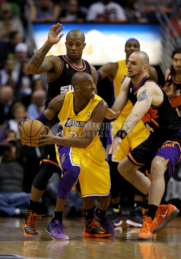 Jan. 30, 2013; Phoenix, AZ, USA: Los Angeles Lakers guard Kobe Bryant (left) controls the ball against Phoenix Suns center Marcin Gortat in the second half at the US Airways Center. The Suns defeated the Lakers 92-86.  Mandatory Credit: Mark J. Rebilas-