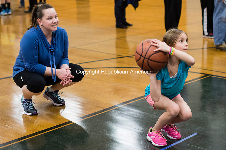 "WOODBURY, CT - 20 November 2015-112015EC19--  Gianna Geraci, 7, tries to sink a free-throw to win Thanksgiving dinner during a ""Turkey Shoot"" at Woodbury Middle School Friday night. Her mother Joy Geraci cheers her on from behind. Depending on how many baskets they made, contestants brought home turkey, pies, stuffing and cranberry sauce. Erin Covey Republican-American."