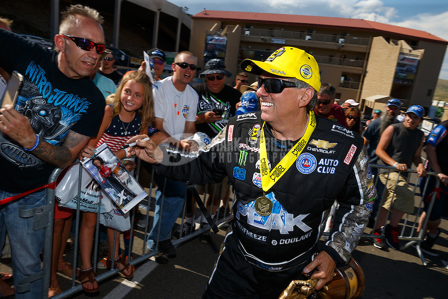 Jul 24, 2016; Morrison, CO, USA; NHRA funny car driver John Force signs autographs for fans as he celebrates after winning the Mile High Nationals at Bandimere Speedway. Mandatory Credit: Mark J. Rebilas-USA TODAY Sports