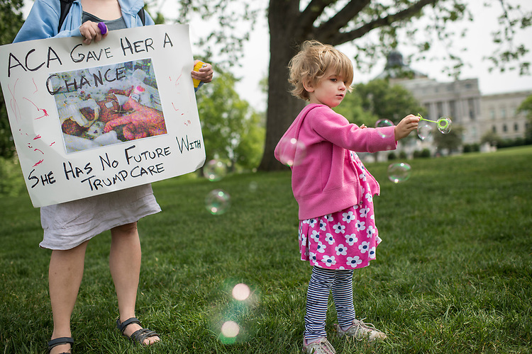 UNITED STATES - MAY 4: Charlie Wood, 4, of Charlottesville, Va., plays with bubbles during rally on the East Front lawn of the Capitol to oppose the House Republicans' bill to repeal and replace the Affordable Care Act on May 4, 2017. She was born 3 1/2 months earlier and her mother Rebecca, at left, holding a picture of Charlie in the hospital, fears changes to the ACA will negatively effect her care. (Photo By Tom Williams/CQ Roll Call)