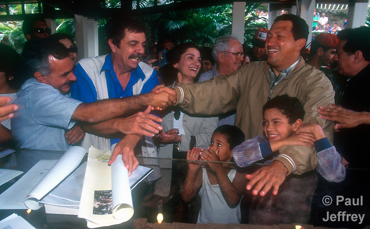 Venezuelan President Hugo Chavez (right) during a visit to the Caracas neighborhood of Catuche in January 2000 following Dec 1999 flooding. Here he meets with local leaders of the Catuche neighborhood redesign project, including Jesuit priest Jose Virtuoso (left), architect Cesar Martin, and Josefina Balbo, president of the National Housing Council.