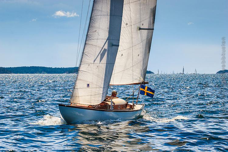 En segelbåt i trä seglar på Kanholmsfjärden Stockholms skärgård. / Stockholms archipelago Sweden.